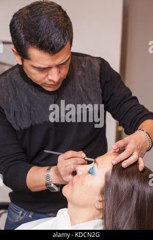 Make up artist applying eyeshadow to a woman - Stock Photo