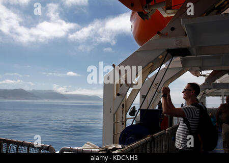 Passenger aboard Interislander Ferry crossing Cook Strait taking photos of Sinclair Head, South of Wellington in - Stock Photo