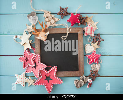 Rustic christmas decorations and ornaments on blue wooden background - Stock Photo
