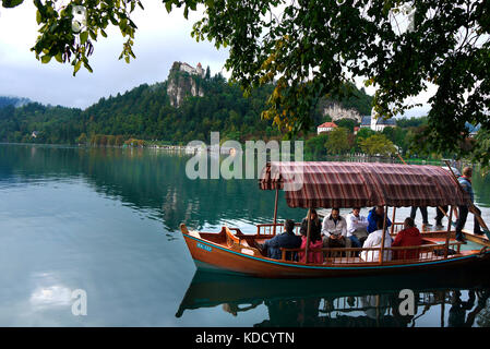 Tourists prepare for a pleasure boat trip round Lake Bled in Bled, Slovenia. In the background is Bled Castle. - Stock Photo