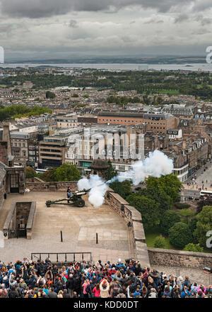 Firing of the One o'clock gun at Edinburgh castle in Scotland. - Stock Photo