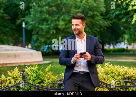A handsome young businessman leaning against the fence in a park while holding his smartphone