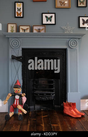 Victorian era cosy, quirky fireplace surround by blue wall, with puppet, quirky orange ankle boots and butterfly - Stock Photo