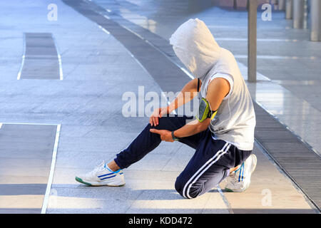 young sport man holding knee with his hands in pain after suffering muscle injury during a running workout - Stock Photo