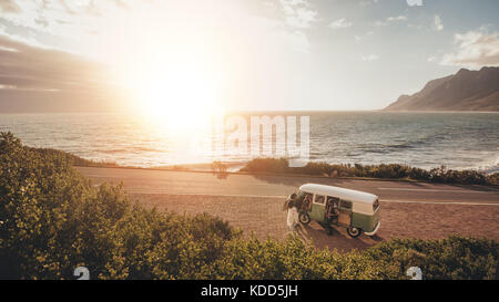 Friends on roadtrip travelling by a van. High angle view of group of people with old minivan standing along coastal - Stock Photo