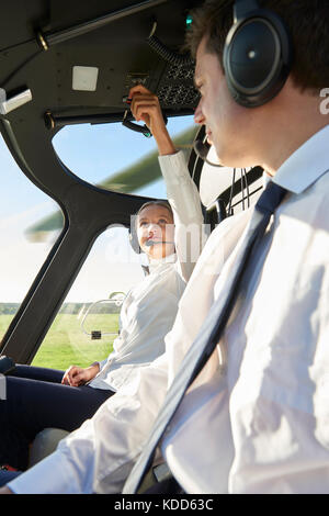 Pilot And Co Pilot In Cockpit Of Helicopter - Stock Photo