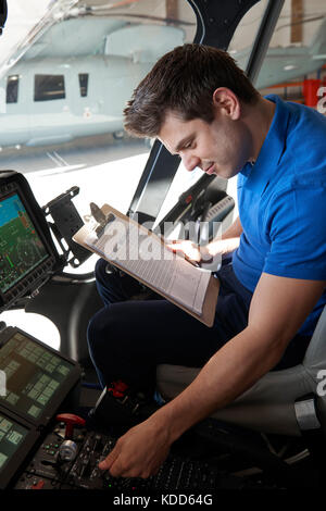 Male Aero Engineer With Clipboard Working In Helicopter Cockpit - Stock Photo
