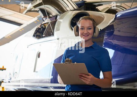 Portrait Of Female Aero Engineer With Clipboard Carrying Out Check On Helicopter In Hangar - Stock Photo