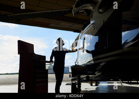 Silhouette Of Male Aero Engineer Working On Helicopter In Hangar - Stock Photo