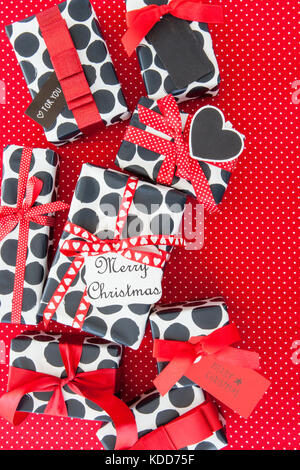 Little presents with red ribbons on red polka dot background - Stock Photo