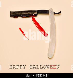 an old and rusty straight razor full of blood and the text happy halloween on an orange background - Stock Photo