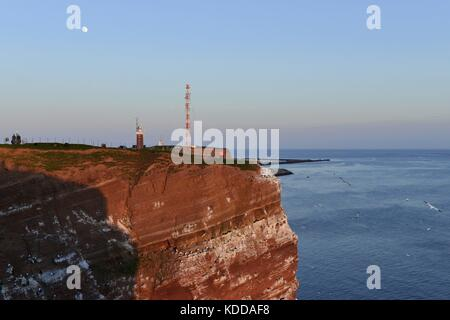 The moon above Heligoland's red rock coast with lighthouse and transmission mast and the North Sea in the depth, - Stock Photo