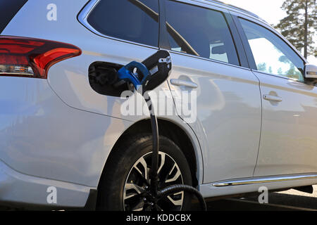 TOIJALA, FINLAND - SEPTEMBER 24, 2017: Detail of white Mitsubishi electric SUV connected to car battery charging - Stock Photo