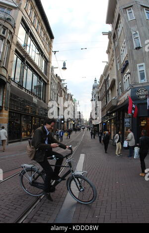 Man crossing the street on his bicycle in Amsterdam - Stock Photo