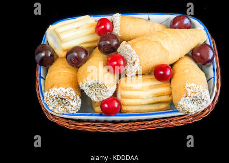 On the napkin on the table ceramic plate with cookies and cherries in a wicker basket. Presented on a dark background. - Stock Photo
