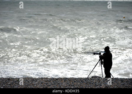 Photographer on a beach in winter, unidentifiable silhouette. - Stock Photo