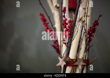 Christmas decoration of bundles of wooden branches with berries and fir cones on a gray background - Stock Photo