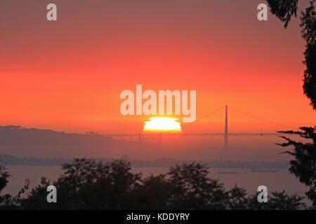 San Francisco, California, USA. 12th Oct, 2017. Bright orange sun sets behind the Golden Gate Bridge in San Francisco, - Stock Photo