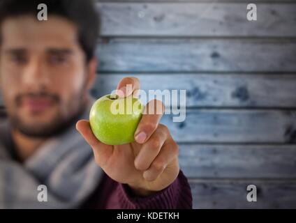 Digital composite of Man against wood with apple and scarf - Stock Photo