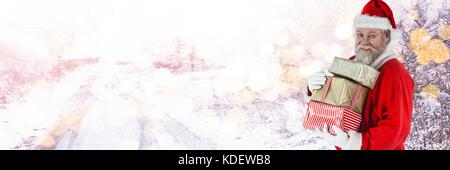 Digital composite of Santa with Winter landscape bearing gifts - Stock Photo