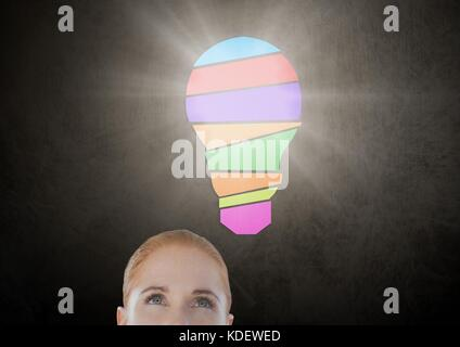 Digital composite of woman looking up at light bulb - Stock Photo
