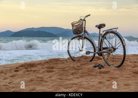 Bicycle on the Beach with Crashing Waves in Nha Trang, Vietnam in Southeast Asia - Stock Photo