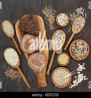 High fiber health food concept with fresh whole grain bread rolls, cereals and grains. Rustic background on oak, - Stock Photo