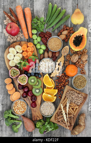 Health food concept for a high fiber diet with fruit, vegetables, cereals, nuts, seeds, whole wheat pasta, grains, - Stock Photo