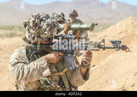 U.S. soldiers fire their weapons during an assault drill at the Fort Irwin National Training Center Alpine Pass - Stock Photo