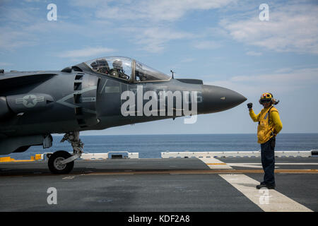 A U.S. sailor signals to a U.S. Marine Corps AV-8B Harrier II ground-attack aircraft launching on the flight deck - Stock Photo