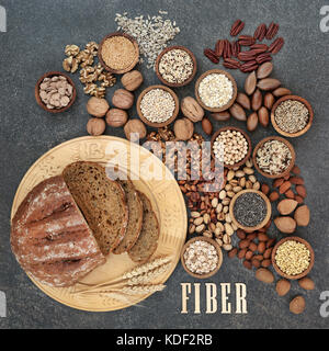 High fibre health food concept with fresh whole grain bread, nuts, seeds, grains and cereals. Foods high in antioxidants - Stock Photo