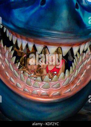 Children, Kids in Jaws Mouth, Shark, Whale, Attraction Disneyworld, Orlando Florida USA - Stock Photo
