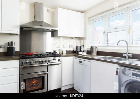 A small, clean, fresh, white kitchen with stainless steel range cooker, back splash & hood in a typical modern UK - Stock Photo