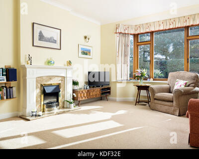 A dated, furnished, sunny living room with fireplace in a home decorated in a style typical of many homes occupied - Stock Photo