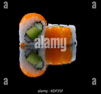 close up of a piece of sushi with glowing and colorful fish eggs on top - Stock Photo