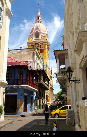 A woman walks down a street in Cartagena, Colombia with the Metropolitan Cathedral Basilica of Saint Catherine of - Stock Photo