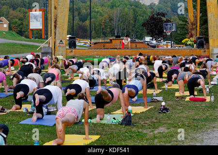 An outdoors yoga class at Mont Sainte Anne in Quebec Canada - Stock Photo