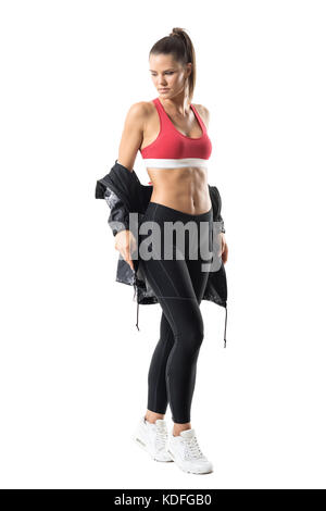 Fitness active woman in leggings taking off tracksuit jacket look back over the shoulder. Full body length portrait - Stock Photo