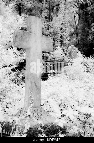 An infrared shot of an old, stone, graveyard cross. - Stock Photo