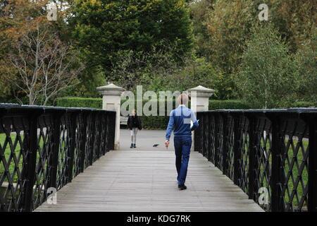 Man dressed in blue walking across the bridge in Regents Park. a woman walks towards him - Stock Photo