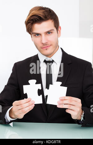 Portrait Of A Young Businessman Solving Jigsaw Puzzle In Office - Stock Photo