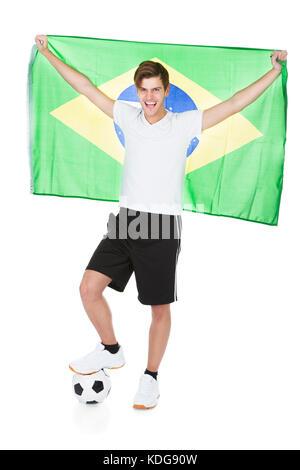 Soccer Player Holding Brazil Flag Over White Background - Stock Photo