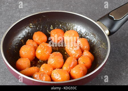 Honey glazed baby carrots with sea salt and thyme in a frying pan on a grey abstract background. Healthy eating - Stock Photo