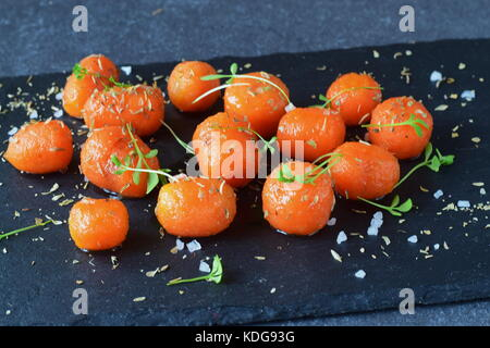 Honey glazed baby carrots with sea salt and thyme in a metal bowl on a grey abstract background. Healthy eating - Stock Photo