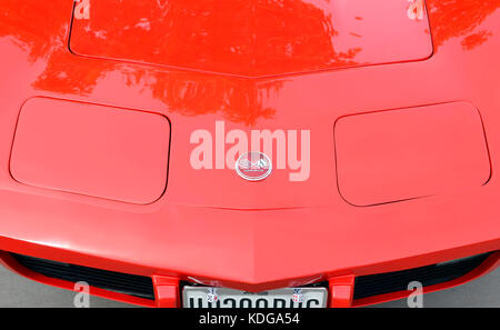 Meeting of classic american cars. Detail of hood with headlights down. Red Chevrolet Corvette C3 Stingray (Made - Stock Photo