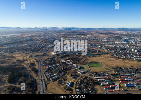 Aerial photograph overlooking Kopavogur town, a suburb of Reykjavik, the capital of Iceland. Mountains in background - Stock Photo