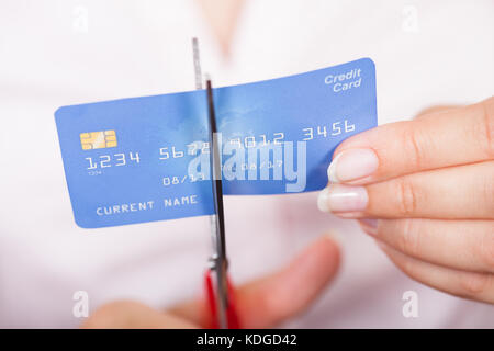 Close-up Of Female Hand Cutting Credit Card With Scissor - Stock Photo