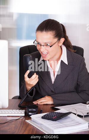 Portrait Of Angry Businesswoman Shouting On Telephone in office - Stock Photo