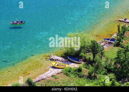 Fishing boat at clear waters of Lake Ohrid surrounding Lin Peninsula in Albania - Stock Photo
