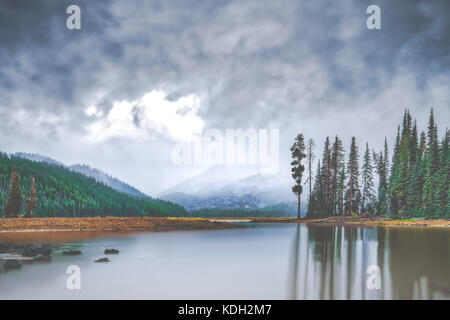 An autumn storm brings early season snowfall to the Cascade Range at Sparks Lake in the Deschutes National Forest - Stock Photo